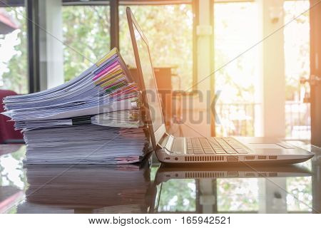 Laptop And Document Stack On Office Desk With Sun Flare