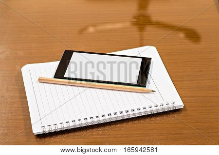 Blank Notebook, Smartphones And Pencil On Wooden Table