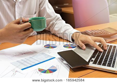 Businessman Holding A Cup Of Coffee And Working On His Plan Project