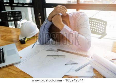 Blurred Image Of Architect Had Depressed On Office Desk