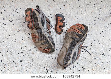 Top view of old sport shoes on terrazzo floor