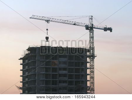 Hoisting tower crane elevates construction detail on building evening view