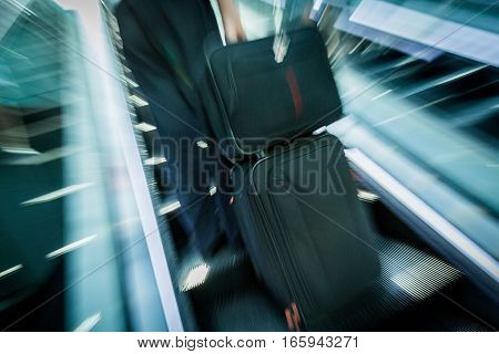 Closeup of People in Airport Carrying Luggage on Escalators
