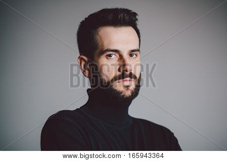Portrait of a handsome bearded young man looking in camera
