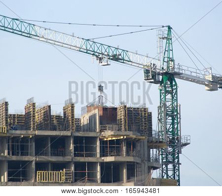Hoisting tower crane elevates construction panel on top of building