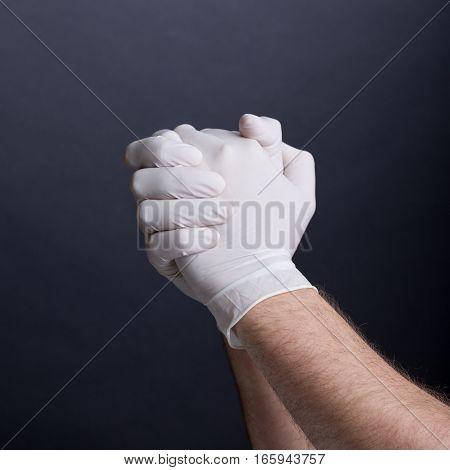 Male hands in latex gloves on dark background