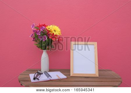 photo Frame on a wooden table and book and Flowers in jar on pink background .