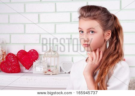 Beauty portrait of girl with big eyes and long hair who looking in front of her in studio with valentines decorations; place for text in the left part of picture