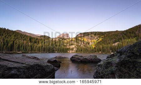 Autumn colors at dawn underneath Hallett Peak, at Bear Lake in Rocky Mountain National Park, near Estes Park, Colorado.