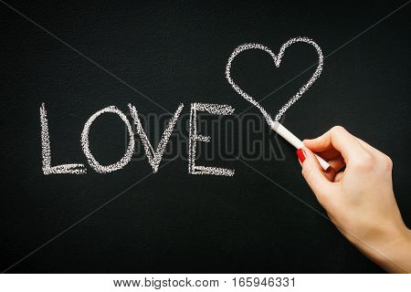 woman's hand writing on the blackboard the word love