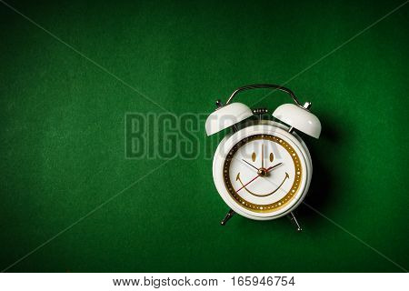 small white clock placed on a green background