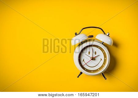 small white clock placed on a yellow background