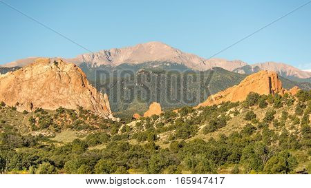 Morning light illuminates Pikes Peak, towering over South Gateway North Gateway Kissing Camels, and the Tower of Babel, in Garden of the Gods, Colorado Springs, Colorado.