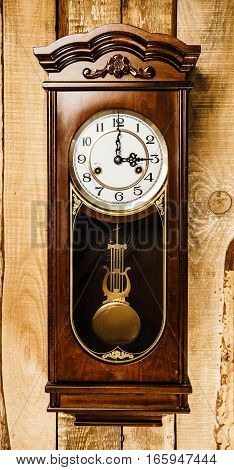 old and big clock hanging on a wooden wall