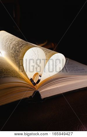 Wedding rings and the book in the rays of bright light