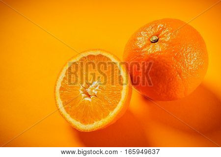 Two fresh and juicy oranges on an orange background