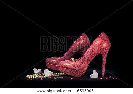 Pink Party Shoes And Hearts On Black Background.