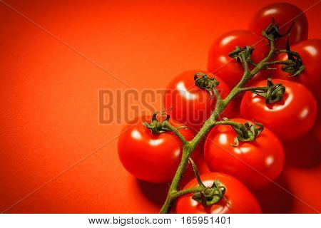 some juicy small tomatoes on a red background
