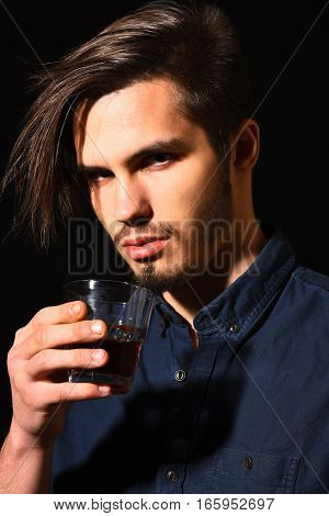 handsome bearded man portrait in blue shirt with stylish hair on serious face holding glass of whisky in black studio background