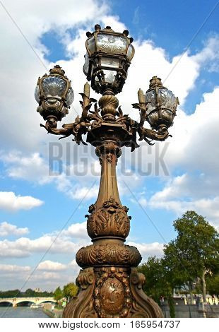 Historical street lamp on the Alexandre III bridge in Paris, France