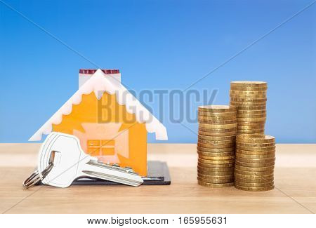 Sale and rental properties loans for real estate concept. Model home with key and coins