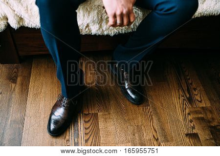 Elegant brown men's shoes and pants on strict man in a sitting position. To prepare for the exit.