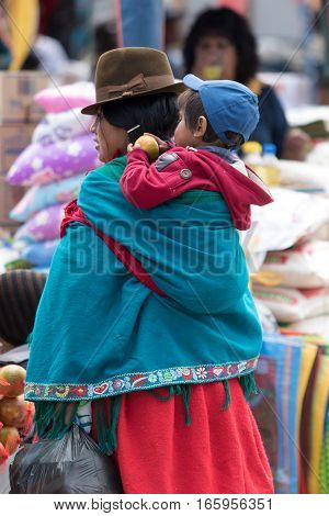 July 24 2016 Alausi Ecuador: indigenous kichwa woman carrying her child on her backk in the local produce market