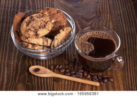 Cup of hot coffee and cookies with chocolate in bowl for breakfast on wooden table
