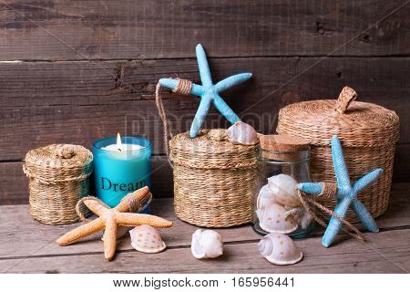Coastal items and candle on aged wooden background. Sea objects. Ocean theme. Vacation concept. Selective focus.