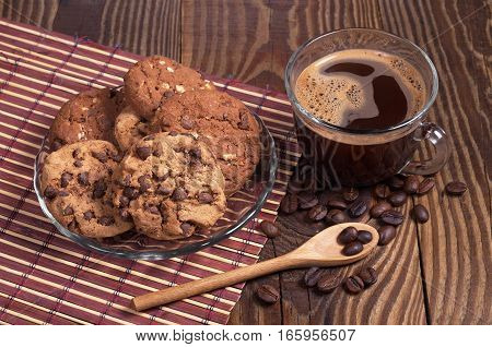 Cup of hot coffee and chocolate cookies in plate on dark wood