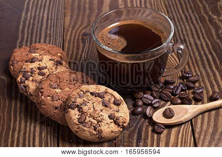 Cup of hot coffee and chocolate cookies on wooden