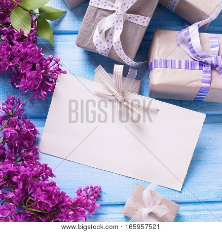 Gift boxes with presents empty tag and lilac flowers on blue wooden background. Selective focus. Place for text. Square image.