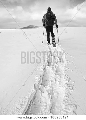Hiker With Backpack Snowshoeing  In Deep Drift. Man With Walk In Hill.