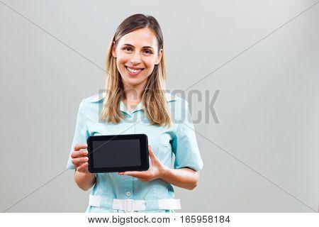 Portrait of beautiful nurse showing digital tablet.