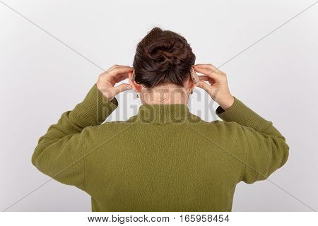 A Woman putting on her hearing aids
