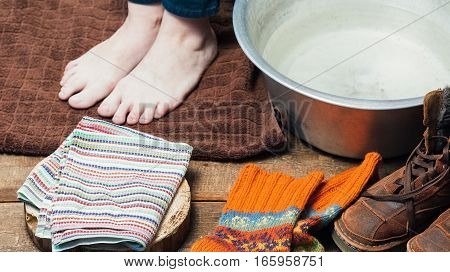 Bare feet on the towel near basin with warm water,  boots and wool socks on the floor after footbath