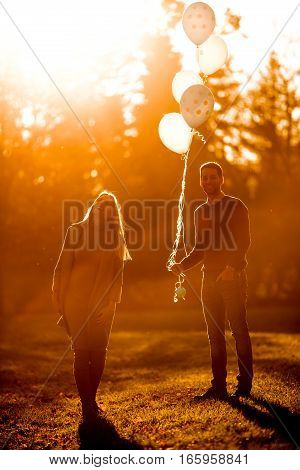 Happy Couple With Balloons In The Autumn Park