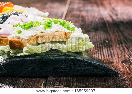 Sandwiches with fresh cheese spread and tops of onions on natural wood board