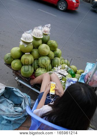 03 january 2017 Long Nget Street 250 phnom penh cambodia young fruit sales woman playing game on smartphone editorial image