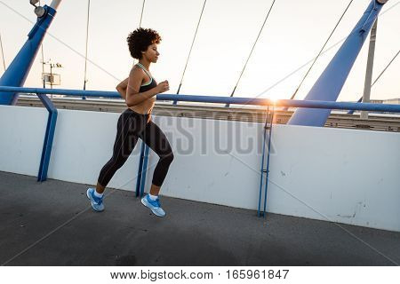 Young woman runner running across city bridge