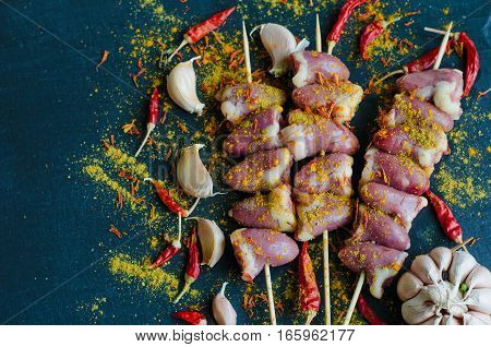 Skewered raw chicken hearts for bbq on black natural slate stone background