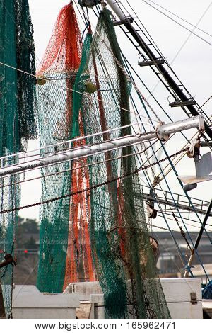 Shrimp fishing vessel with colorful nets of orange, green and black.
