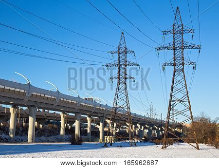 Industrial urban landscape with a transmission tower and the Western High Speed Diameter overpass. Saint-Petersburg Russia