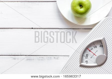 floor scale and apple on wooden background top view.