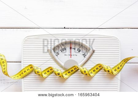 floor scale and centimeter to measure on wooden background top view.