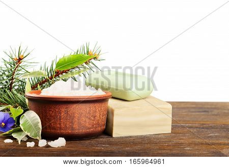 Aromatic bath salt in a clay cup and soap on a wooden background