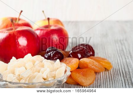 Ripe red apples dates and dried fruits on a wooden background