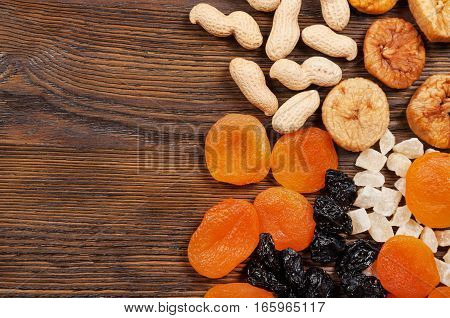 Peanuts and dried fruits on a wooden background