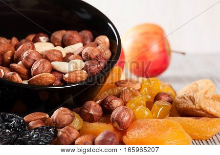 Dried fruits lemon apricot fig and nuts in black plate on a wooden background.