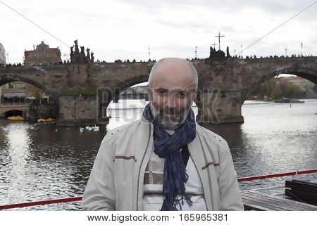 Portrait of a smiling bearded man standing on board a small ship on the background of the Charles Bridge in Prague